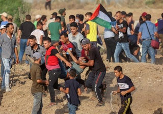 Palestinian protesters evacuate an injured youth amid clashes with Israeli security forces at the Gaza border fence, Saturday.